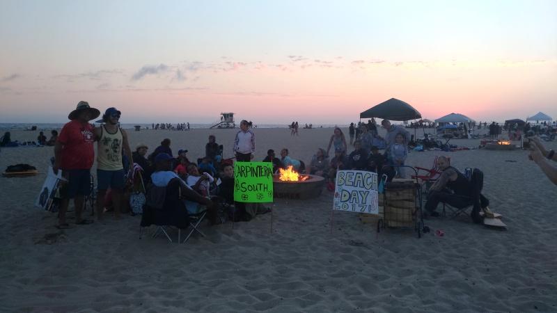 Skupina lidí s billboardy sedí na pláži.
