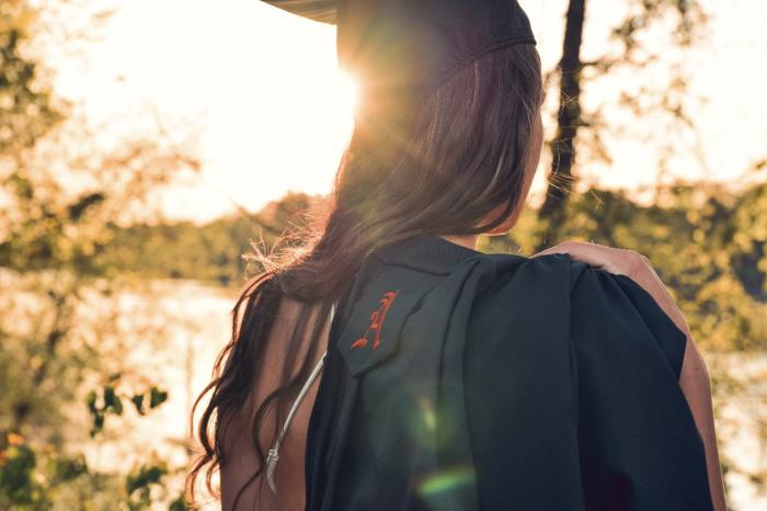 Studentka s baťohem při západu slunce