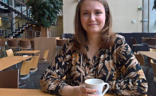 Studentka pije kávu ve školní kavárně